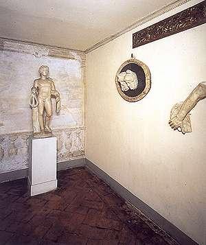"""Stanzino dell'Apollo, foto della sala con un pregevole fregio ligneo dell'inizio del XVI secolo, un braccio marmoreo,,un ovale di marmo nero con due teste e un """"Apollino"""" di marmo."""